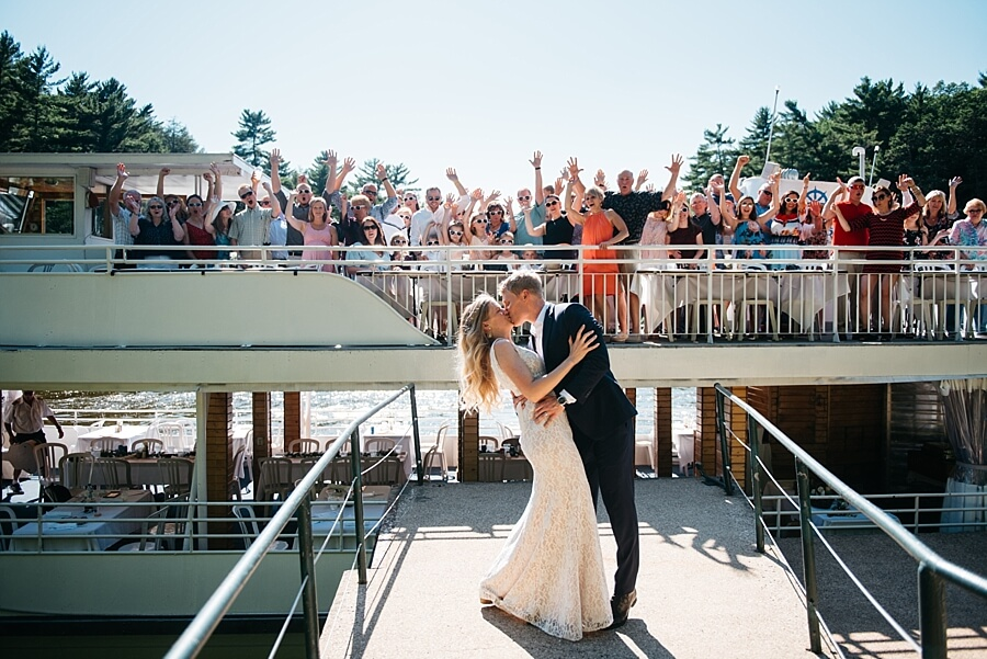Bride and Groom kissing in front of the Winnebago dinner cruise boat filled with guests on the Wisconsin River in Wisconsin Dells